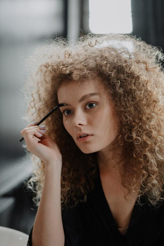 Девушка красит брови
