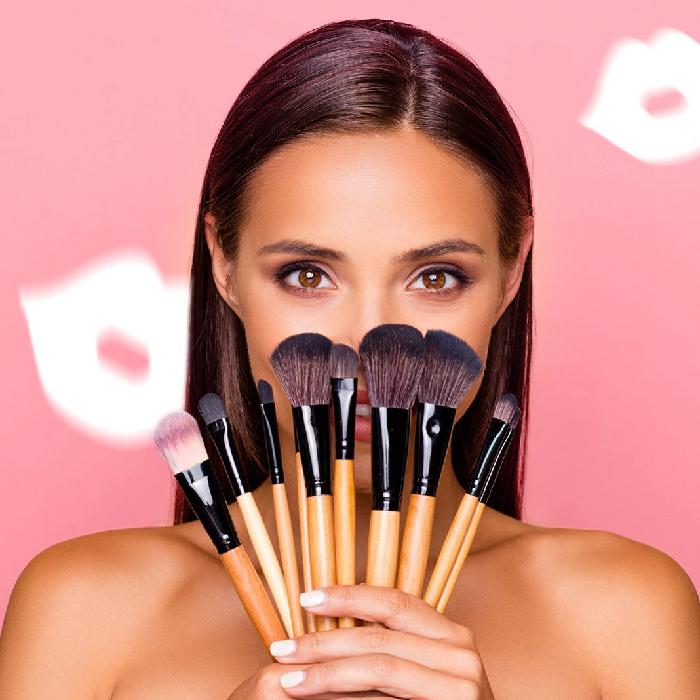 Девушка прикрывает лицо кистями для макияжа